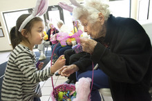 Paul Fraughton | The Salt Lake Tribune. Three-year-old Malaiah Martinez holds a chocolate egg she picked out of the Easter basket given to her by Ida Painter, who will turn 100 in September. Seniors from Emeritus Senior Living Center brought 30 hand- filled  Easter baskets to children at The Road Home, Salt Lake's homeless center.  Monday, April 2, 2012 Paul Fraughton / Salt Lake Tribune    Monday, April 2, 2012