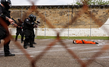 Trent Nelson  |  The Salt Lake Tribune Weber State student Sarah Cleverley lies prone, role playing as an inmate while an emergency response team from the Chemung County (NY) Sheriff's Office moves in during a training scenario at the Mock Prison Riot, Monday, May 7, 2012 at the West Virginia Penitentiary in Moundsville, West Virginia.
