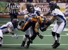 Lennie Mahler  |  The Salt Lake Tribune Utah Blaze's Aaron Lesue is tripped up by Talon defenders as he runs for extra yards against the San Antonio Talons on Saturday, May 26, 2012, at EnergySolutions Arena.