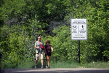 Kim Raff   The Salt Lake Tribune (left) David Mackay and Sohayla Jewett  walk past one of the new signs installed on the City Creek Trail for bikers and pedestrians in Salt Lake City, Utah on May 25, 2012.