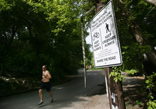 Kim Raff   The Salt Lake Tribune A jogger runs past one of the new signs installed on the City Creek Trail for bikers and pedestrians in Salt Lake City, Utah on May 25, 2012.