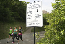 Kim Raff   The Salt Lake Tribune People walk past one of the new signs installed on the City Creek Trail for bikers and pedestrians in Salt Lake City, Utah on May 25, 2012.