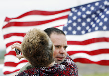 ADVANCE FOR USE MONDAY, MAY 28, 2012 AND THEREAFTER - FILE - In this Saturday, April 14, 2012 file photo, Army Pvt. Randy Donovan is hugged by his mother, Twila Donovan, upon arriving at the Crossroads Christian Church in Hutchinson, Kan. for a welcome home party. Donovan was injured by an IED in Afghanistan in November 2011. His injuries included a fractured vertebra in his neck, a broken upper jaw and broken radius in his right elbow. He also had shrapnel wounds to his upper body and two broken vertebrae in his back. Donovan received a Purple Heart. The cost of veterans' benefits and health care peaks decades after a war ends, says Harvard University economist Linda Bilmes. These peaked in 1969 for veterans from World War I and in the 1980s for World War II. They haven't peaked yet for Vietnam veterans. (AP Photo/The Hutchinson News, Lindsey Bauman)