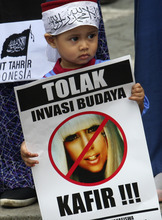 A Muslim boy holds a poster bearing a defaced picture of U.S. pop singer Lady Gaga during a protest against her concert that is scheduled to be held on June 3, in Jakarta, Indonesia, Thursday, May 24, 2012. Lady Gaga might have to cancel her sold-out show in Indonesia because police worry her sexy clothes and dance moves undermine Islamic values and will corrupt the country's youth. The writing on the poster reads