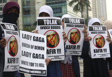 Muslim women hold posters during a protest against Lady Gaga's concert that is scheduled to be held on June 3, in Jakarta, Indonesia, Thursday, May 24, 2012. Lady Gaga might have to cancel her sold-out show in Indonesia because police worry her sexy clothes and dance moves undermine Islamic values and will corrupt the country's youth. The writings on the posters read
