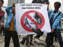 Muslim protesters throw shoes at a defaced poster of US pop singer Lady Gaga during a protest against her concert that is scheduled to be held on June 3, in Jakarta, Indonesia, Thursday, May 24, 2012. Lady Gaga might have to cancel her sold-out show in Indonesia because police worry her sexy clothes and dance moves undermine Islamic values and will corrupt the country's youth. The writing on the poster reads