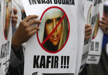 A Muslim woman holds a poster bearing a defaced picture of U.S. pop singer Lady Gaga during a protest against her concert that is scheduled to be held on June 3, in Jakarta, Indonesia, Thursday, May 24, 2012. Lady Gaga might have to cancel her sold-out show in Indonesia because police worry her sexy clothes and dance moves undermine Islamic values and will corrupt the country's youth. The writing on the poster reads