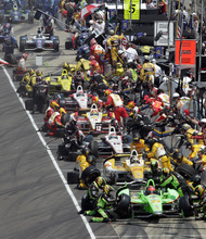 IndyCar drivers, front to back, James Hinchcliffe, of Canada; Ryan Hunter-Reay; Will Power, of Australia; Helio Castroneves, of Brazil; Ryan Briscoe, also of Australia; and Josef Newgarden receive service on the first pit stop during the running of the 96th Indianapolis 500 auto race at the Indianapolis Motor Speedway in Indianapolis, Sunday, May 27, 2012. (AP Photo/AJ Mast)