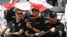 IndyCar drivers Josef Newgarden, left, Helio Castroneves, of Brazil, and Will Power, of Australia, seek some refief from the sun under a broken umbrella during the drivers meeting for the Indianapolis 500 auto race at the Indianapolis Motor Speedway in Indianapolis, Saturday, May 26, 2012. The 96th running of the race is Sunday where temperatures are expected in the min 90's. (AP Photo/Darron Cummings)