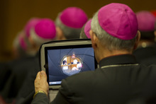 A bishop uses his tablet to take pictures as Pope Benedict XVI addresses the plenary assembly of the CEI, Italian Bishops' Conference, at the Vatican, Thursday, May 24, 2012. (AP Photo/Andrew Medichini)