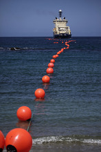 FILE - In this Jan. 22, 2011 file photo, a fiber-optic cable, suspended from buoys, is rolled out by a specialized ship off La Guaira, Venezuelan coast.  Cuban officials last year welcomed the arrival of the undersea fiber-optic cable linking the country to Venezuela, which was supposed to boost web capacity 3,000-fold. Even a retired Fidel Castro had hailed the dawn of a new cyber-age on the island. More than a year later, the government barely speaks of the cable anymore and Cuba's internet connection is still the slowest in the hemisphere. (AP Photo/Ariana Cubillos, File)