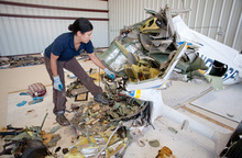 Jud Burkett | The Spectrum Zoë Keliher, an air safety investigator with the National Transportation Safety Board, explains the process behind her investigation into the crash of the single engine plane in which four people were killed early Saturday as she combs through the wreckage inside a hangar at the St. George Airport Monday, May 28, 2012.