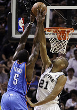 San Antonio Spurs center Tim Duncan (21) defends as Oklahoma City Thunder center Kendrick Perkins (5) shoots during the first quarter of Game 1 in their NBA basketball Western Conference finals playoff series, Sunday, May 27, 2012, in San Antonio. (AP Photo/Eric Gay)