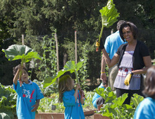 HOLD FOR RELEASE AT 12:01 A.M. TUESDAY, MAY 29, 2012, AND THEREAFTER WITH STORY SLUGGED: MICHELLE OBAMA BOOK - FILE - In this June 3, 2011 file photo, first lady Michelle Obama pretends that a rhubarb plant is an umbrella with a group of children during an event at the White House garden in Washington. From the beginning, Obama's kitchen garden has been an overachiever, churning out more peppers, parsley and eggplant than expected, and generating interest that _ yes, really _ crosses oceans. (AP Photo/Evan Vucci, File)