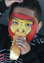 Rick Egan  | The Salt Lake Tribune   Four-year-old Soni Vainuku, West Valley,  enjoys his free hot dog, after having his face painted at the Valley View cemetery in West Valley, Monday, May 28, 2012. Valley VIew Cemetery offers free hot dogs and sodas to people visiting their family's graves, as well as face painting.