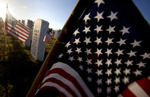 American flags wave near Marine Lance Cpl. Michael Harris' grave marker, center, as the the sun rises over Georgia National Cemetery Monday, May 28, 2012, in Canton, Ga. Harris died Feb 6, 2012 while serving in Afghanistan. (AP Photo/David Goldman)