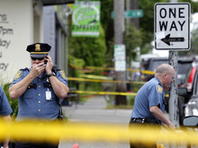 A Seattle Police officer talks on his radio at left outside Cafe Racer, where a gunman opened fire, killing two people and critically wounded three others, Wednesday, May 30, 2012, in Seattle. Police are searching for the gunman, described as a man in his 30s wearing dark clothes. (AP Photo/Ted S. Warren)