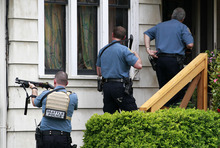 Police approach a house in the University district in Seattle close to where a gunman killed two people and critically wounded three others at a cafe Wednesday, May 30, 2012. They left shortly after. Not long after a gunman opened fire at the cafe in the north Seattle neighborhood, a woman was shot to death in downtown Seattle and her car taken and later abandoned in Seattle's West Seattle neighborhood. It was not immediately clear if the incidents were connected. (AP Photo/Elaine Thompson)