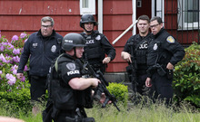 Police stand near a house in the University district in Seattle close to the cafe where a gunman killed two people and critically wounded three others Wednesday, May 30, 2012. Not long after the shooting, a woman was shot to death in downtown Seattle, her car taken and later abandoned in Seattle's West Seattle neighborhood. It was not immediately clear if the two events are connected. (AP Photo/Elaine Thompson)