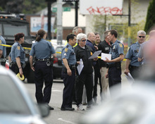 Seattle Police officers confer outside Cafe Racer, where a gunman opened fire, killing two people and critically wounded three others, Wednesday, May 30, 2012, in Seattle. Police are searching for the gunman, described as a man in his 30s wearing dark clothes. (AP Photo/Ted S. Warren)