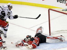 Los Angeles Kings' Anze Kopitar (11), of Slovenia, shoots a puck past New Jersey Devils goalie Martin Brodeur (30) for the winning goal in overtime of Game 1 of the NHL hockey Stanley Cup finals Wednesday, May 30, 2012, in Newark, N.J.  (AP Photo/Frank Franklin II)