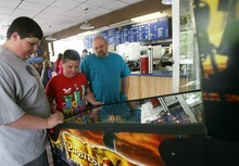 Kim Raff | The Salt Lake Tribune Dawson, left, Ean and Jake Brown play at a pinball machine at the Dairy Delight in Tooele.