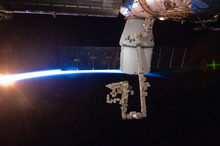 In this image provided by NASA with rays of sunshine and the thin blue atmosphere of Earth serving as a backdrop, the SpaceX Dragon commercial cargo craft is berthed to the Earth-facing side of the International Space Station's Harmony node Sunday May 27, 2012. Expedition 31 Flight Engineers Don Pettit and Andre Kuipers grappled Dragon at 9:56 a.m. (EDT) with the Canadarm2 robotic arm and used it to berth Dragon to the at 12:02 p.m. May 25, 2012. Dragon became the first commercially developed space vehicle to be launched to the station. Dragon is scheduled to spend about a week docked with the station before returning to Earth on May 31 for retrieval. (AP Photo/NASA)