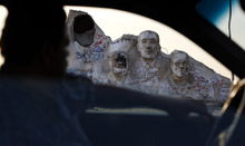 A motorist passes a statue showing the defaced likeness of ousted President Hosni Mubarak, left, as well as Egyptian Nobel prize winner Ahmed Zewail, second left, the late Egyptian President Anwar Sadat, second right, and at right Egyptian novelist and Nobel Prize Winner Naguib Mahfouz, in 6th of October city, Egypt, Thursday, May 23, 2012. Guilty or not, Saturday's verdict in the Hosni Mubarak trial may only add to Egypt's polarization. The country is bracing for a heated runoff for president pitting the ousted leader's protege and last prime minister against an Islamist from a group that the old regime repeatedly cracked down. (AP Photo/Fredrik Persson)