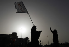 A Bahraini anti-government protester carries a flag with the image of a man who died in the past 15 months of a pro-democracy uprising during a rally Thursday, May 31, 2012, in Abu Saiba, Bahrain. A few hundred people participated in the rally, calling for freedom for political prisoners and democracy in the Gulf kingdom, before dispersing peacefully. (AP Photo/Hasan Jamali)