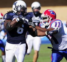 Utah State running back Robert Turbin (6) is pushed out of bounds by Louisiana Tech corner back DeMarcion Evans (11) during an NCAA college football game Saturday, October, 22, 2011, in Logan, Utah. Louisiana Tech won 24-17. (AP Photo/The Herald Journal, Tyler Larson)