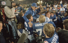 Brigham Young University football coach LaVell Edwards carries the trophy as he is carried off the field following BYU's 24-17 victory over University of Michigan in the Holiday Bowl, Dec. 22, 1984 in San Diego. (AP Photo/Phillip Davies)