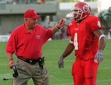 Utah coach Ron McBride has a hand out for running back Marty Johnson after Johnson scored a TD. Utah faces Utah State in the season opener Saturday night. photo by Trent Nelson. 09/01/2001