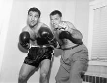Ex-heavyweight champion Jack Dempsey, right, strikes a familiar pose with heavyweight Rocky Marciano during visit to Rocky's training camp at Grossinger in New York on Sept. 9, 1952. Rocky is training at the upstate spot for his Sept. 23, title bout with champion Jersey Joe Walcott in Philadelphia, Pa. Jack said the bout