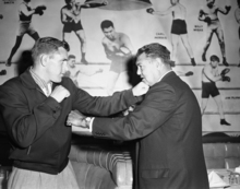 Daniel Hodge, left, the Olympic Wrestler and Golden Gloves Heavyweight champ who announced he has turned professional fighter, squares off with former Heavyweight Champion Jack Dempsey at a luncheon honoring Hodge, May 12, 1958, New York. (AP Photo)