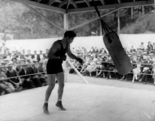 Heavyweight boxer Jack Dempsey punches the heavy bag as spectators watch at his training camp at Saratoga Lake, N.Y., on July 6, 1927.  (AP Photo)