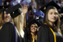 Trent Nelson  |  The Salt Lake Tribune Graduates wave to family and friends during the Processional at Westminster College's Commencement Saturday, June 2, 2012 at the Maverik Center in West Valley City.