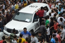In this citizen journalism image taken on Tuesday, May 29, 2012 and provided by Edlib News Network ENN, Syrians gather around a U.N. observers vehicle during a demonstration in Kfarnebel, Idlib province, northern Syria. U.N. Secretary-General Ban Ki-moon called on Syria on Thursday to stop its attacks, saying the U.N. observers monitoring the cease-fire were not there to watch the killing of innocent people. (AP Photo/Edlib News Network ENN) THE ASSOCIATED PRESS IS UNABLE TO INDEPENDENTLY VERIFY THE AUTHENTICITY, CONTENT, LOCATION OR DATE OF THIS HANDOUT PHOTO