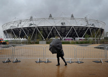 A woman struggles with an umbrella as the heavy rain falls outside the Olympic Stadium, in London Wednesday April 18, 2012.  Wednesday marks 100 days before the London 2012 Olympic Games  begin. (AP Photo/Anthony Devlin/PA)