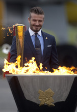 British soccer player David Beckham holds the Olympic torch lit from the lantern carried onboard a special British Airways flight BA 2012, after lighting the cauldron following its arrival at Royal Naval Air Station Culdrose, west of England, from Greece, Friday, May 18, 2012. (AP Photo/Alastair Grant)