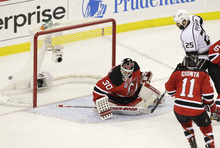 The puck flies into the net past New Jersey Devils' Martin Brodeur (30) for the winning goal during the overtime period of Game 2 of the NHL hockey Stanley Cup finals against the Los Angeles Kings, Saturday, June 2, 2012, in Newark, N.J. Kings' Dustin Penner (25) and Devils' Stephen Gionta (11) look on. The Kings won 2-1. (AP Photo/Kathy Willens)