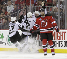 New Jersey Devils' Steve Bernier, right, skates past celebrating Los Angeles Kings after the Kings won 2-1 in Game 2 of the NHL hockey Stanley Cup finals on Saturday, June 2, 2012,in Newark, N.J. (AP Photo/Frank Franklin II)
