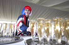 A woman takes her glass of free champagne part of a special picnic for some 10,000 people which forms part of the Queen's Diamond Jubilee celebrations at Buckingham Palace in London, Monday, June  4, 2012. (AP Photo/Alastair Grant, Pool)