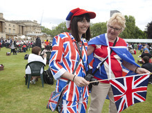 Jayne Littlewood and her mother Anne Randle pose for photos wearing a union jack suit as they enjoy a special picnic in the grounds of Buckingham Palace, seen behind,  as the Queen's Diamond Jubilee celebrations continue in London, Monday, June  4, 2012. (AP Photo/Alastair Grant, Pool)