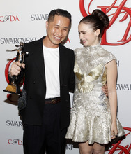 Designer Phillip Lim poses with actress Lily Collins backstage after winning the Swarovski Award for Menswear at the CFDA Fashion Awards on Monday, June 4, 2012 in New York. (Photo by Jason DeCrow/Invision/AP)