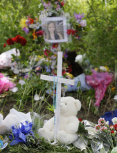 A cross is part of a memorial Monday, June 4, 2012 at the crash scene for four teens who died near Brunswick, Ohio. A fourth victim of the crash, Kevin Fox, died Monday, a day after he was thrown from a car just hours before his high school graduation in a northeast Ohio crash that killed three other teens. A car carrying Fox and four other teenagers went airborne, crashed, and flipped onto its roof at a railroad crossing early Sunday. (AP Photo/Tony Dejak)