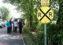 People gather at the scene of an early-morning crash on Boston Road in Lorain County, Ohio to pay their respects and mourn three teens who died there, Sunday, June 3, 2012. A car carrying five teenagers went airborne as it sped over railroad tracks in northeast Ohio early Sunday and crashed, killing the 18-year-old driver hours before his high school graduation and two of his passengers, the Ohio State Highway Patrol said. (AP Photo/The Plain Dealer, Peggy Turbett) MANDATORY CREDIT; NO SALES