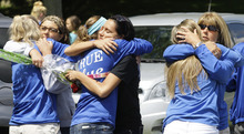 Brunswick High school students hug Monday, June 4, 2012 at the crash scene for four teens who died in a car crash over the weekend near Brunswick, Ohio. A fourth victim of the crash, Kevin Fox, died Monday, a day after he was thrown from a car just hours before his high school graduation in a northeast Ohio crash that killed three other teens. A car carrying Fox and four other teenagers went airborne, crashed, and flipped onto its roof at a railroad crossing early Sunday. (AP Photo/Tony Dejak)