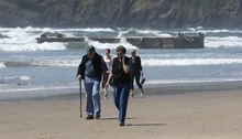 People walk along the beach as waves pound the massive dock that washed ashore on Agate Beach Wednesday, June 6, 2012, in Newport, Ore.  A nearly 70-foot-long dock that floated ashore on an Oregon beach was torn loose from a fishing port in northern Japan by last year's tsunami and drifted across thousands of miles of Pacific Ocean, a Japanese Consulate official said Wednesday.  (AP Photo/Rick Bowmer)