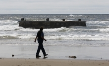 A woman looks at the massive dock that washed ashore on Agate Beach Wednesday, June 6, 2012, in Newport, Ore.  A nearly 70-foot-long dock that floated ashore on an Oregon beach was torn loose from a fishing port in northern Japan by last year's tsunami and drifted across thousands of miles of Pacific Ocean, a Japanese Consulate official said Wednesday.  (AP Photo/Rick Bowmer)