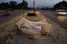 Vehicles move past Pakistani day laborers, sleeping under a mosquito net, in the middle of a street in Islamabad, Pakistan, early Monday, June 4, 2012. (AP Photo/Muhammed Muheisen)